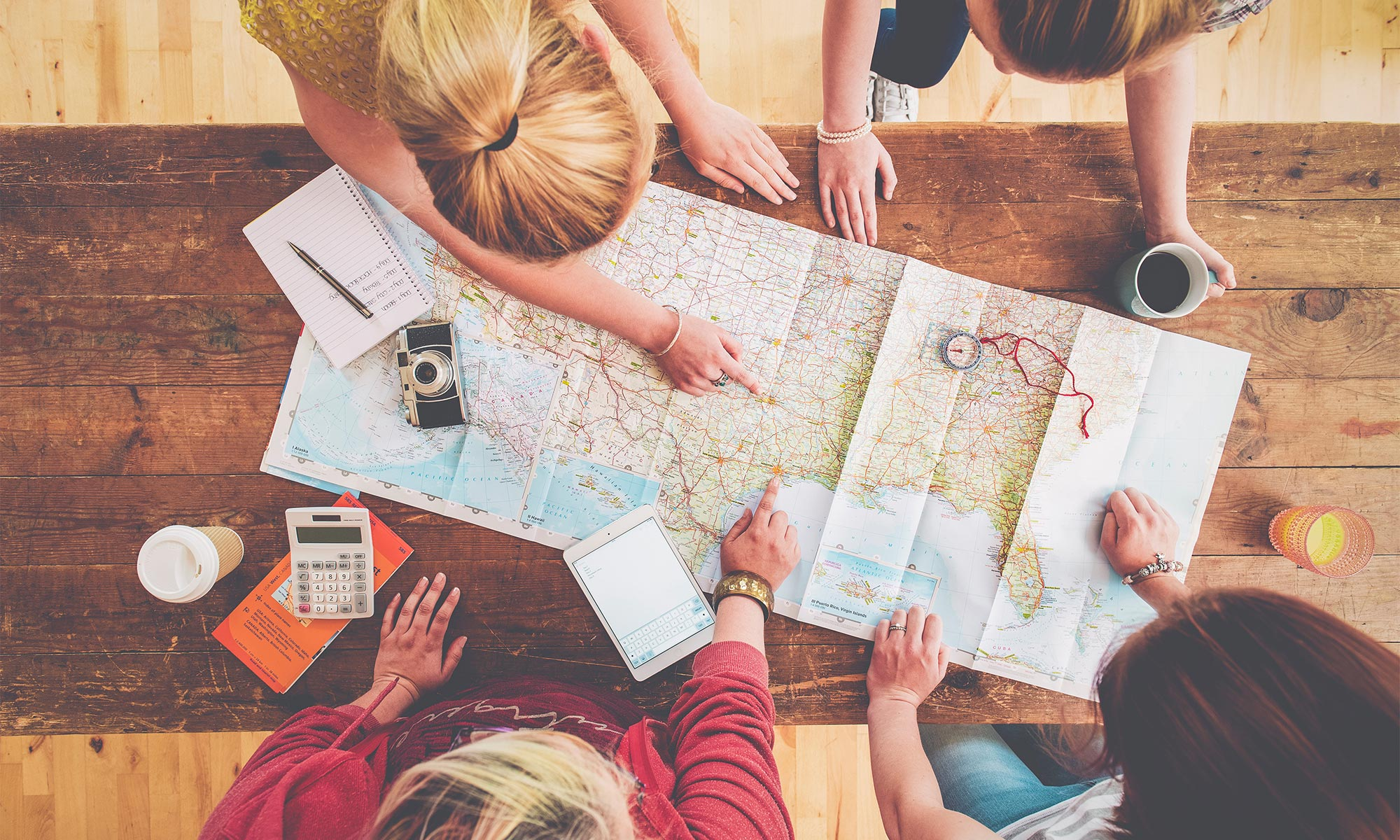 Women planning trip with map on wooden table.